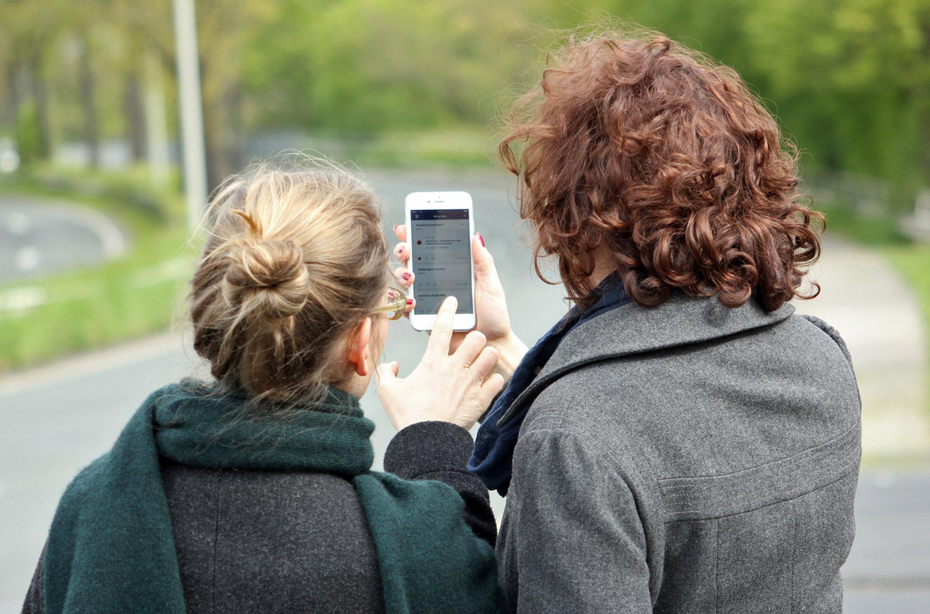 Zwei Frauen schauen sich die Warn-App NINA auf einem Smartphone an.