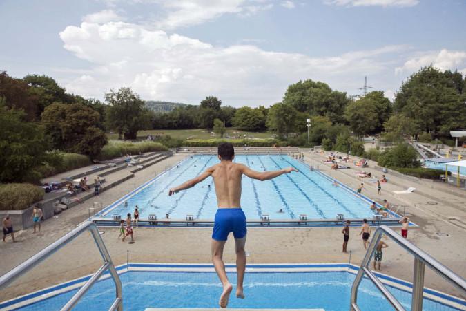 Ein Jugendlicher springt vom Sprungturm ab. Im Hintergrund ist das Schwimmerbecken zu sehen. Foto: Ulrike Klumpp