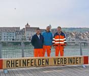Uwe Röschke (Mitte), Tommaso Gioia (links) und Giuseppe Pepe (rechts) bei der Douglasienbank am Rhein.