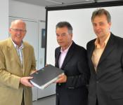 Bürgermeister Rolf Karrer (links) überreicht Kurt Grieshaber und Ulf Tonne (rechts) die Baugenehmigung für den Logistik Park.