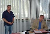 Oberbürgermeister Klaus Eberhardt unterzeichnet im Beisein von Christian Rooks, Leiter der städtischen Baurechtsabteilung, die Baugenehmigung.