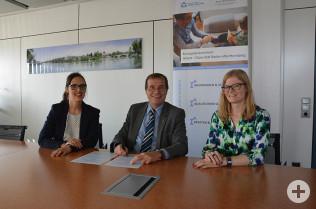 Oberbürgermeister Klaus Eberhardt unterschreibt die Rahmenvereinbarungen. Links Lucill Simak und rechts Inga Autzen (Kompetenzzentrum Arbeit Diversität)