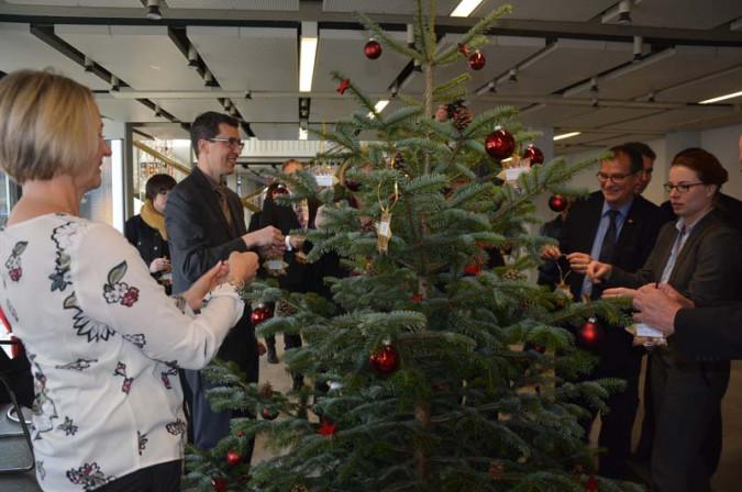 """Mit viel Freude schmückten die Bündnispartner den Weihnachtsbaum im Eingangsbereich des Rathauses mit den """"Rheinfelder Sterntalern""""."""