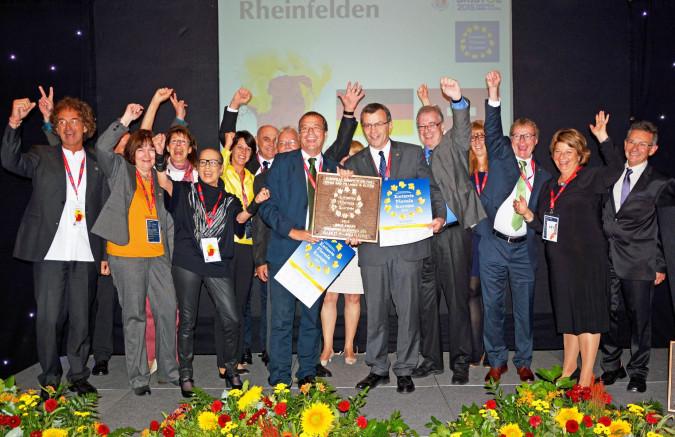 Oberbürgermeister Klaus Eberhardt, Stadtammann Franco Mazzi und weitere Vertreter der beiden Rheinfelden freuen sich über die Entente Florale Europe Auszeichnung in Gold.