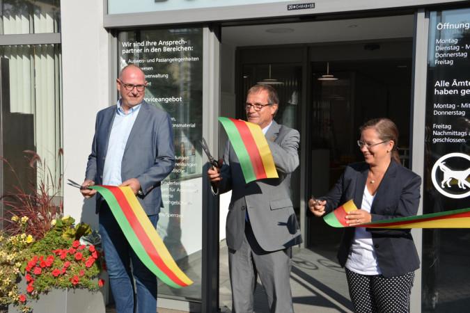 Der Leiter des Bürgerbüros, Frank-Michael Littwin, durchschneidet gemeinsam mit Oberbürgermeister Klaus Eberhardt und Bürgermeisterin Diana Stöcker symbolisch ein Band zur Wiedereröffnungs des Bürgerbüros.