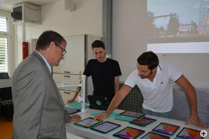 Oberbürgermeister Klaus Eberhardt lässt sich von Roberto Redina (IT Abteilung der Stadtverwaltung) und dem Lehrer an der Goetheschule, Jonas Baumann, verschiedene Lernapps auf dem iPad zeigen.
