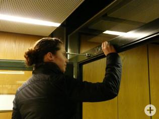Die Sternsingerin schreibt die Segensbitte über die Tür zum Sitzungssaal.
