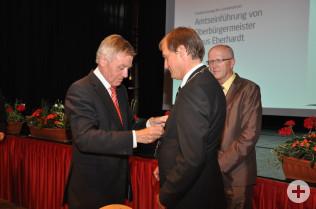 Eberhard Niethammer (links) überreicht Klaus Eberhardt die Amtskette. Im Hintergrund steht Bürgermeister Rolf Karrer.