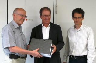 Bürgermeister Rolf Karrer (rechts) übergibt Architekt Rudolf Vogel und Projektleiter Thomas Rauter die Baugenehmigung.