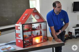 Rene Stach demonstriert mit dem Rauchhaus, wie sich der Rauch verteilt.