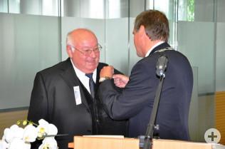 Oberbürgermeister Klaus Eberhardt heftet Gerhard Vogel die Ehrennadel des Lands Baden-Württemberg an die Brust.