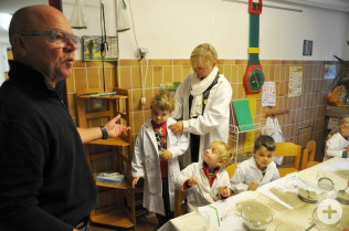 Helmut Bär freut sich, dass die neuen Kittel bei den Kiddies so gut ankommen. Erzieherin Angelika Tresp hilft beim Anziehen.