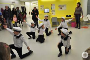 Kinder tanzten in Matrosenanzügen.
