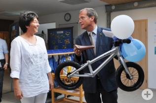 Oberbürgermeister Klaus Eberhardt überreicht ein Kinderlaufrad.